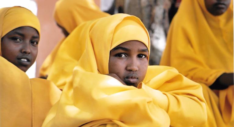 Girl in yellow hijab sits among peers